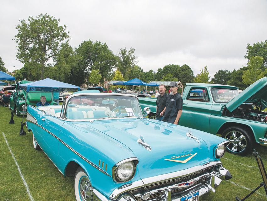 "A 1957 Chevrolet Bel Air convertible attracts onlookers, during Northglenn's Annual 4th of July Car Show, at E. B. Rains, Jr. Memorial Park. Owner Andy Wilson of Arvada, says the vehicle is painted ""Tropical Turquoise"", and was originally manufactured in St. Louis, MO."