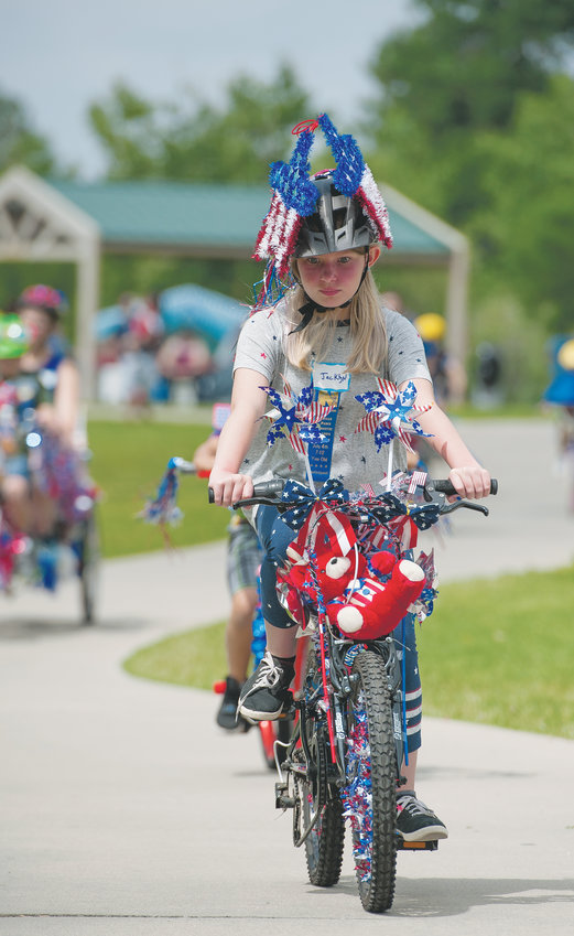 Jacklyn Dettling, 10, of Milliken, rides the pedestrian/cyclist trail, which circles Webster Lake, at E. B. Rains Jr. Memorial Park, during the Pedals and Paws event of the city's annual 4th of July celebration. Dettling is the granddaughter of Kathy and George Shellbaker of Northglenn, who've seen many of their children and grandchildren, participate in the event.