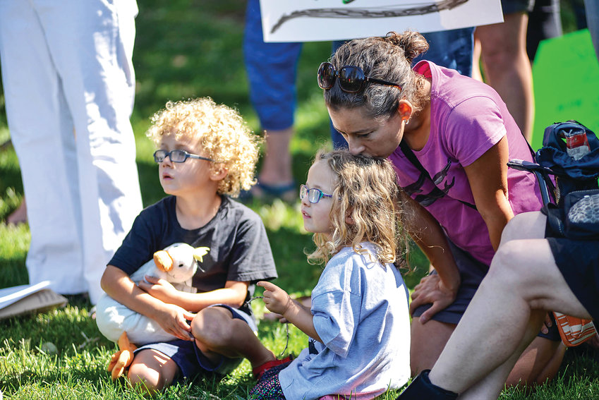 Moses (Left) and Adela watch their father, Justin Marceau, speak to the group of protesters under the watch of their mother Rebecca Aviel in Washington Park, Saturday morning, July 6, 2019.