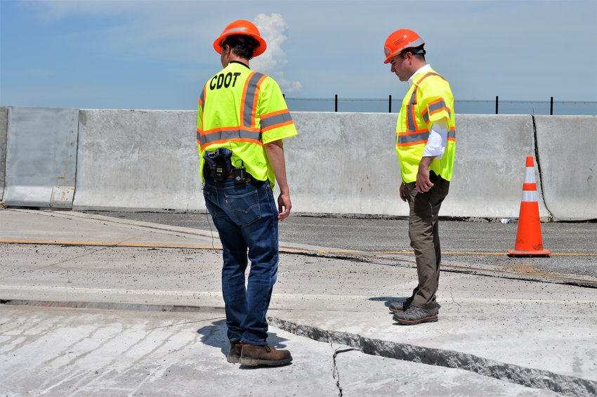 Chief Engineer Joshua Laipply, left, and Regional Communications Manager Matt Inzio stand on either side of a crack that formed in U.S. 36 beginning July 12. Officials think wet soil below the road caused a slope failure, leading to the crack in the road.