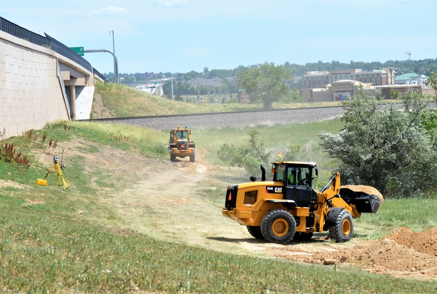 Dump trucks and loaders work to load dirt on the western side of U.S. 36 in an effort to counterbalance a slope failure there and stop damage to the highways southeastern-bound lanes July 13.