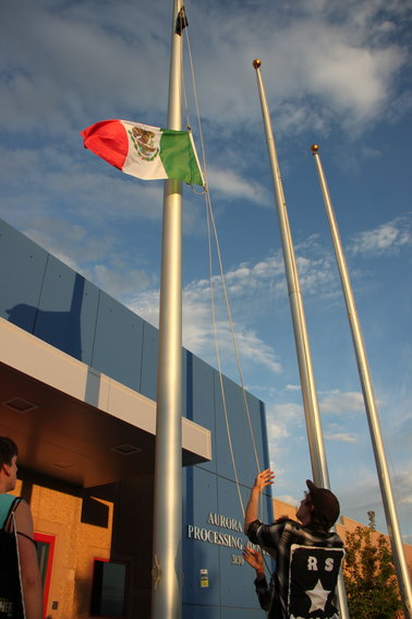 A protester raises the Mexican flag outside Aurora's immigrant detention center.