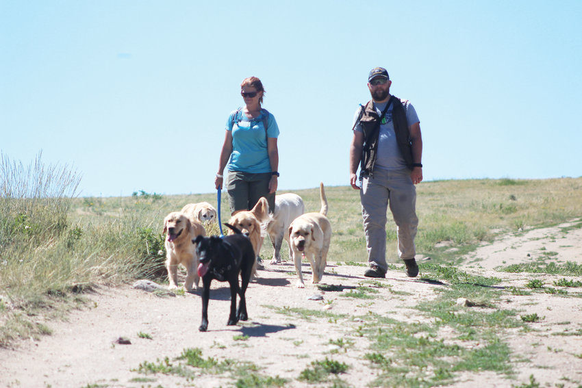 Tracy, a dog walker, and Kyle Hawkins, with his black dog Trinket, finish a walk along the Glendale Open Space Trail July 15. Tracy is from Golden with clients in Denver and said the Glendale Open Space is the biggest around, besides Cherry Creek, which is why it's her favorite spot.