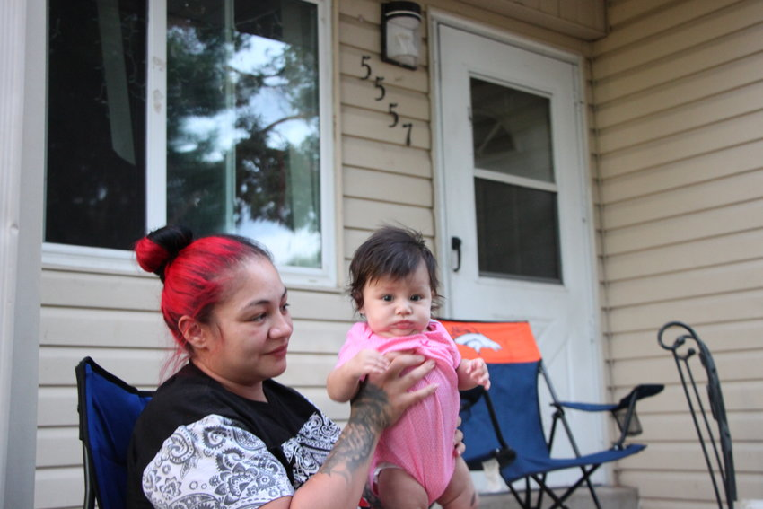 Jackie Chavez, left, holds her three-month-old daughter Serenity in front of their north Littleton home. South Metro Housing Options, which owns Chavez's two-bedroom duplex, plans to submit a request to the federal government that would allow them to demolish or sell dozens of public housing units around Littleton.