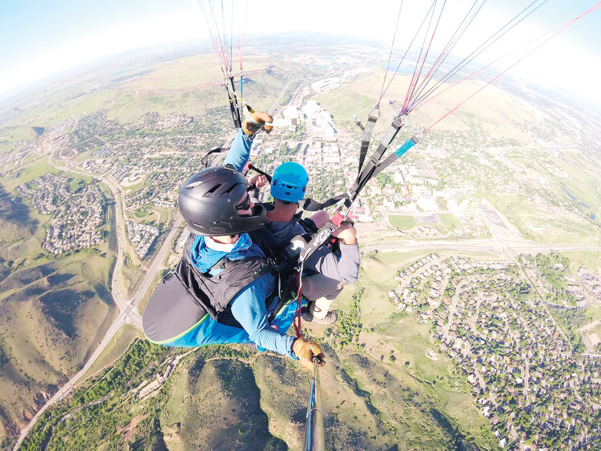 A GoPro captures a picture of David Hach, in the back, co-owner of Paraglide Tandem, as he and a passenger soar over Golden on a recent flight. Some people go tandem paragliding to cross something off a bucket list and some do it to get over a fear of heights, Hach said, but a flight also tends to be a popular birthday gift.