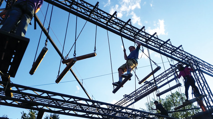A couple of people navigate a challenge on Adventure Golf & Raceway's ropes course in 2017. People enjoy the attraction for the physical challenge, as well as to gain a sense of accomplishment.