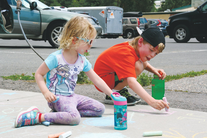 Daisy, 4, and Hunter, 7, Maness of Golden participate in ARTSWEEK GOLDEN's Chalk on the Creek on July 12. Daisy was coloring in a blueberry ice cream cone while her brother Hunter was drawing Kapow the Cow, a cartoon character he invented.