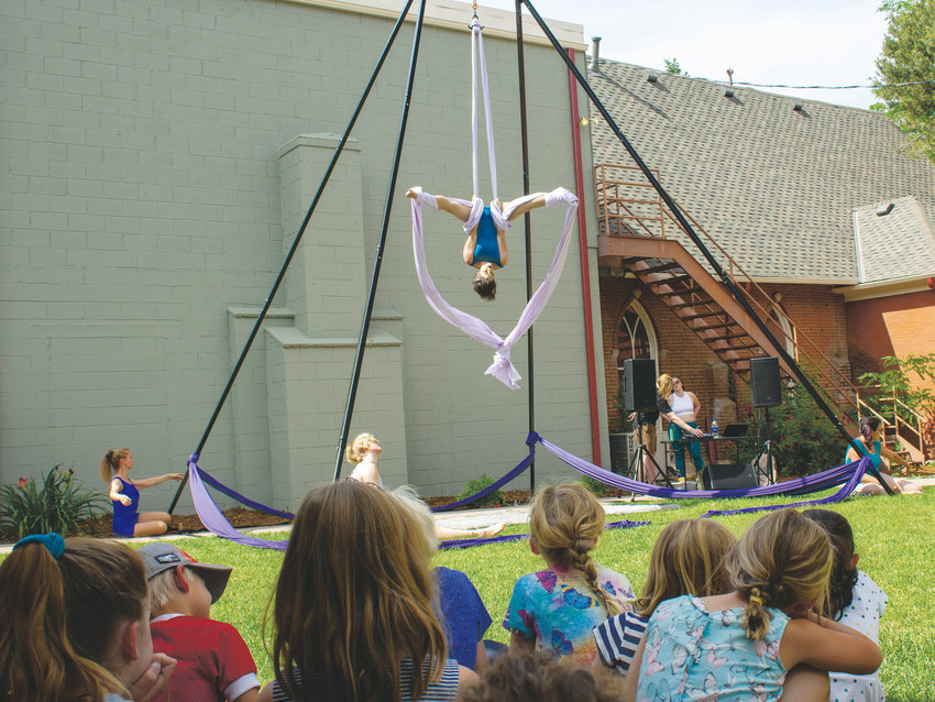 A group of children watch an aerialist from Apex Aerialists perform during the second annual Plein Air Event Exhibit on July 11 in the courtyard at Foothills Art Center, 809 15th St., in Golden.