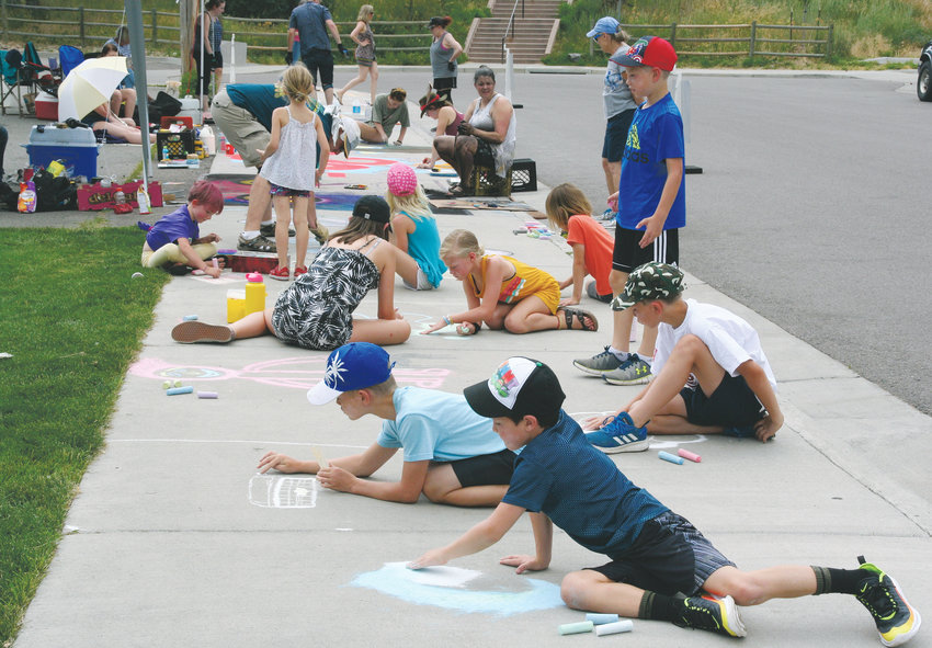 A group of seven siblings and cousins, ranging in age from 8-13, all of Wheat Ridge and Arvada, create some original artwork during ARTSWEEK GOLDEN's Chalk on the Creek on July 12. The youths came to the event with their grandmother Terri Miller of Arvada.
