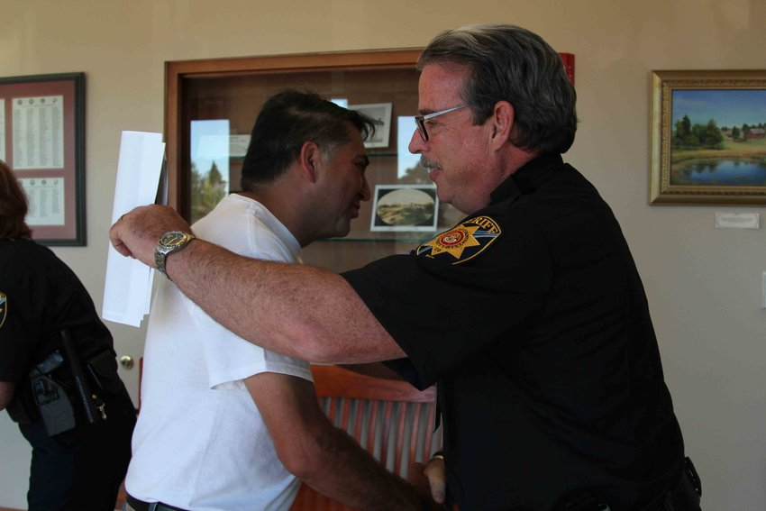 John Castillo goes in to hug Sheriff Tony Spurlcok before a July 16 Board of County Commissioners work session.