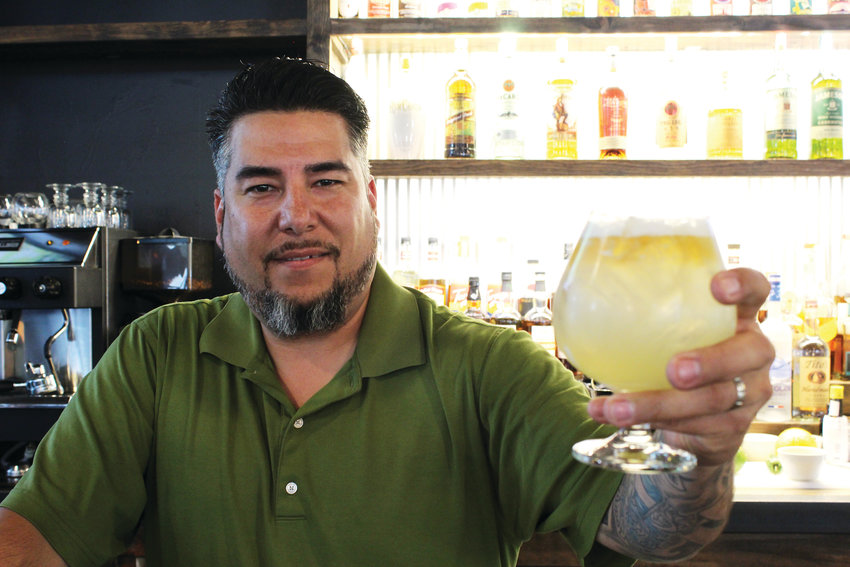 "Fabian Valdez and his signature drink, ""The IV,"" which includes Tingala liqueur, tequila, pineapple-ginger-turmeric CBD kombucha, fresh lime juice, and simple syrup. Valdez, a former Army medic, recently opened Outpost Eatery, a gastropub in Lone Tree."