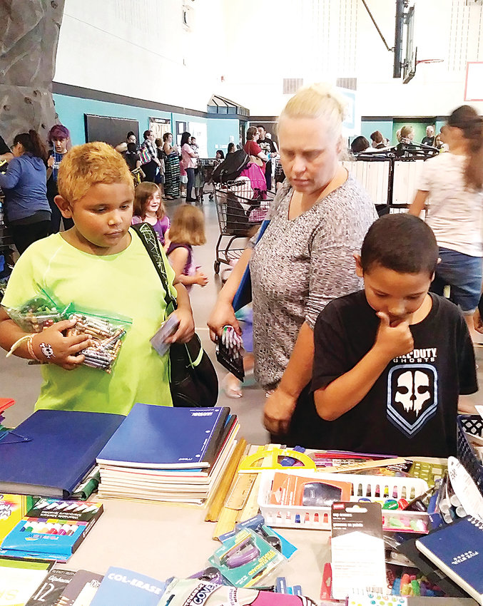 Community members select supplies for the upcoming school year during the Action Center School Supply Distribution in 2018.