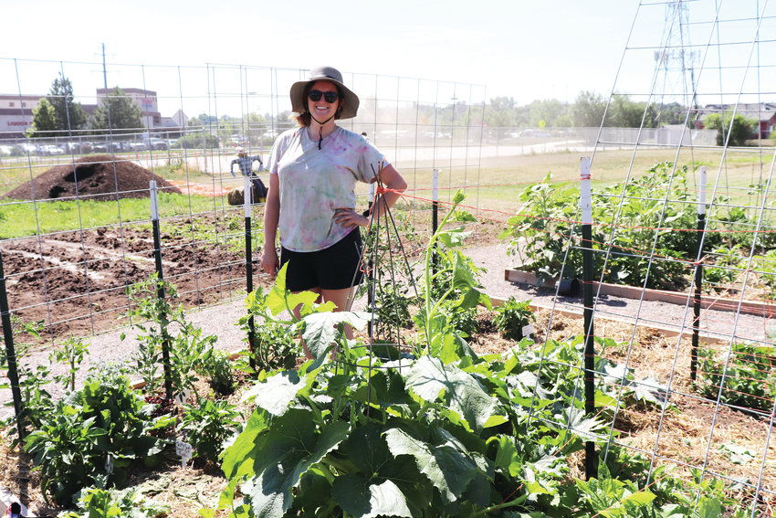 Arvada resident MacKenzie Keller stands in her community garden plot, where she is growing more than 15 different plants and vegetables this year.