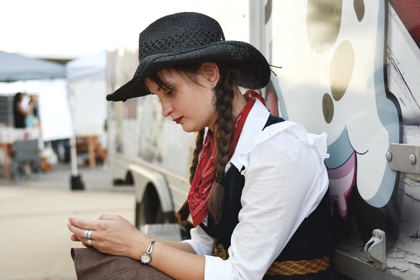 "Sandra McNeill, 22, of Vancouver Island, BC, checks her cellphone during a break from performing in the ""The Cutest Show on Earth"" at the 2017 Adams County Fair in Brighton."