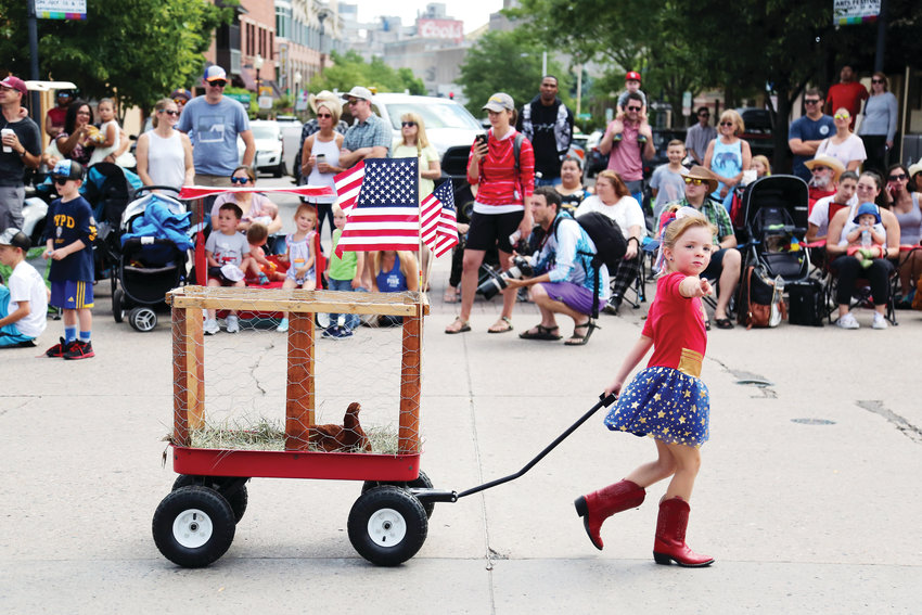 Gigi Acree, 5, walks the Buffalo Bill Day Parade in Golden with her chicken in tow.