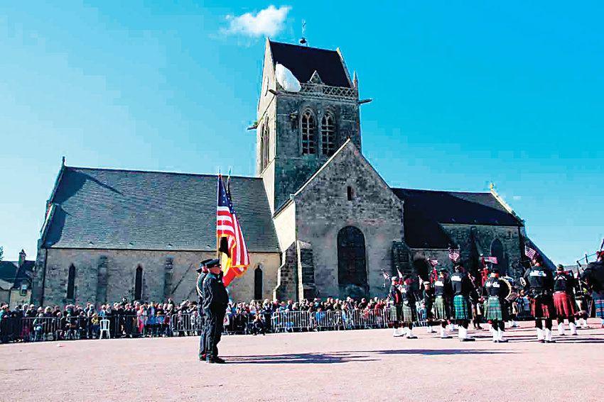 Members of the Colorado Emerald Society play in St. Mere Eglise, where a dummy of a paratrooper hangs from the church in remembrance of a paratrooper who became caught there during the battle of D-Day, but survived.