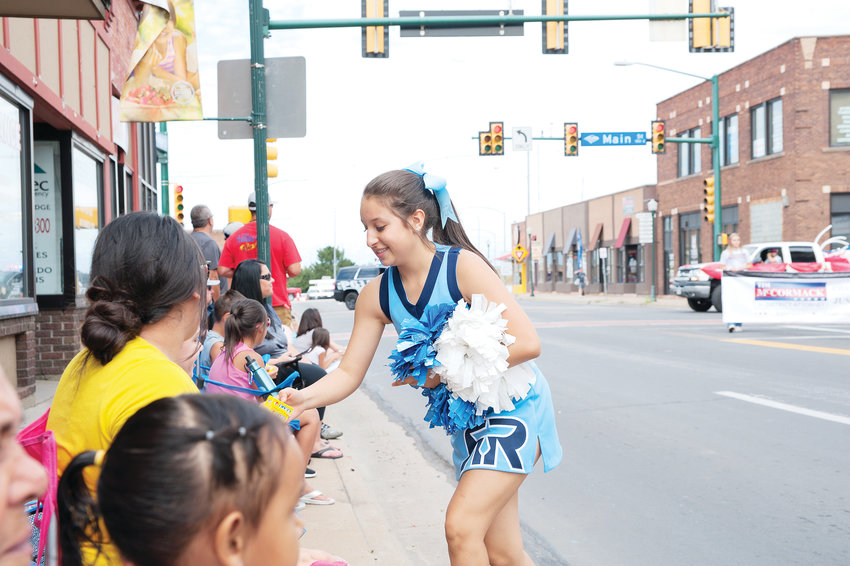 Riverdale Ridge cheerleader Pam Lerma hands out candy during last Saturday's annual Adams County Fair Parade in downtown Brighton. The fair runs August 4th at Adams County Regional Park.