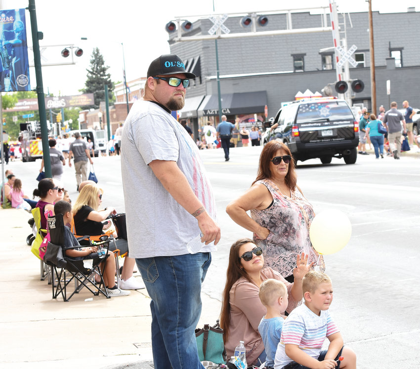 Brandon Bunjes of Thornton and family, await the official Adams County Fair parade float carrying his mother Nancy Bunjes, and sister Alyssa Bunjes Baker, both former Adams County Fair Queens, from 1980 and 1992 respectively. The annual parade was held July 27 in downtown Brighton, in front of a sparse crowd.