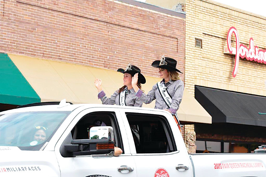 Adams County Fair Queen Racheal Lampo, right, of Thornton, and Lady-in-Waiting, Mandy McCormick of Bennett, waive to spectators during the annual Adams County Fair Parade July 27 in Brighton.
