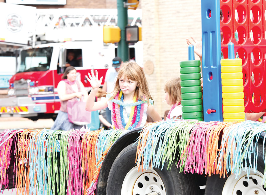 A young rider waves from a children's float during Adams County Fair Parade, in downtown Brighton July 27.