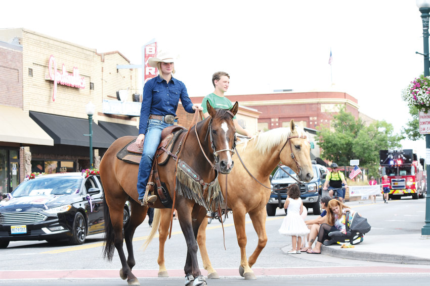 A pair of young riders and their horses make the turn from Main Street to Bridge Street in Brighton, the annual Adams County Fair Parade July 27.