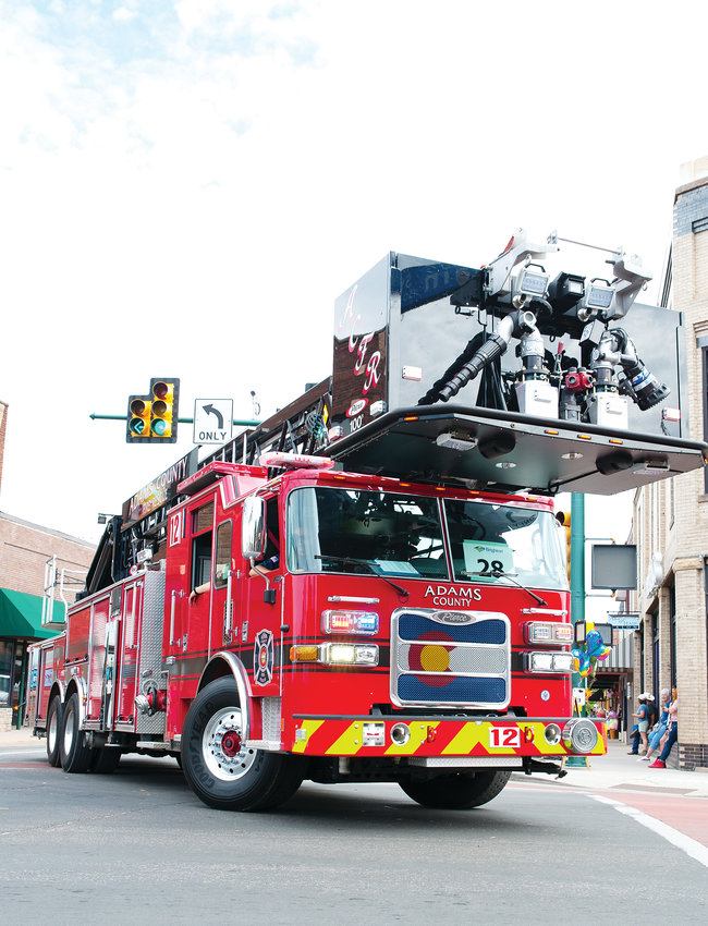 An Adams County fire truck makes the turn from Main onto Bridge Street, July 27th Adams County Fair Parade in downtown Brighton.