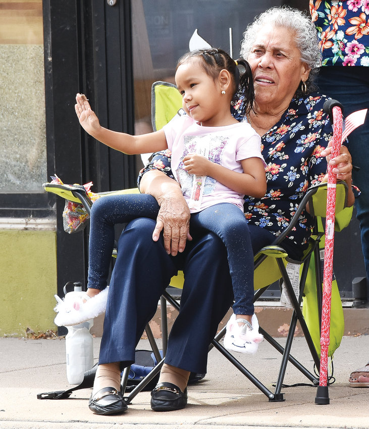 Francisca Lopez and her granddaughter Renee Rubio, 3, both of Brighton, watch the Adams County Fair Parade along Bridge Street in Brighton on July 27. Parade crowds were lower than in previous years.