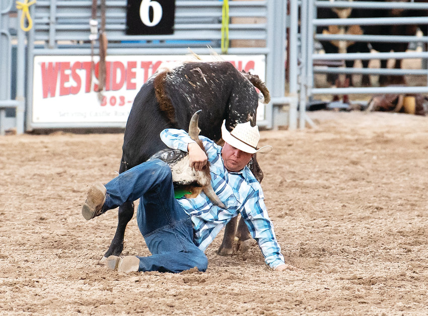 Buck Rinehart, of Bennet, pulls down his target during the steer wrestling event.
