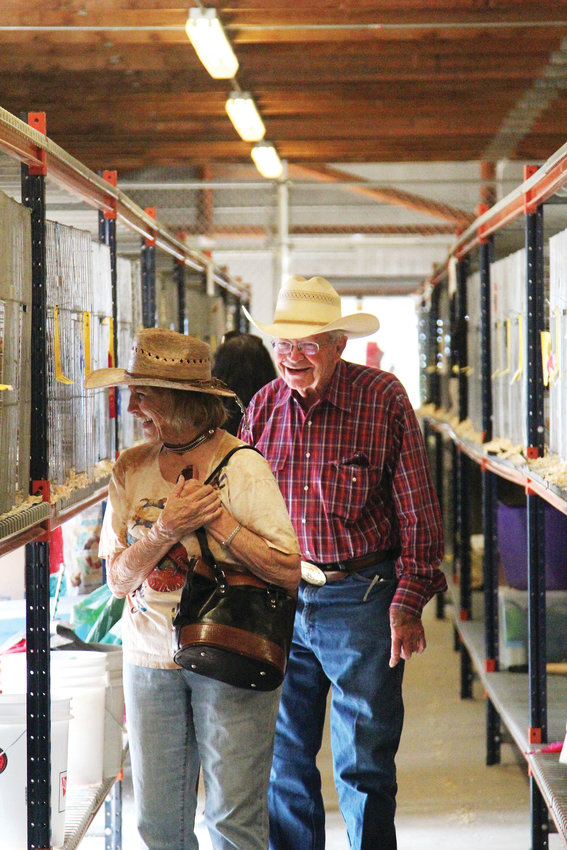 Judy Lowery and Dale Mikelson, long-time friends who graduated high school together, have a laugh learning about chickens on the poultry barn at the Douglas County Fair & Rodeo.