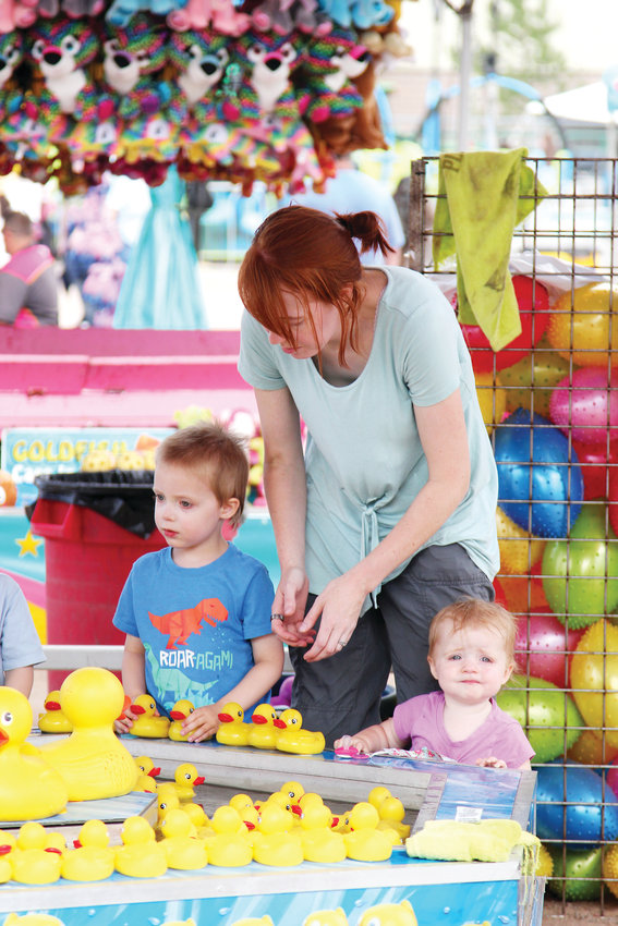 Stephanie Smith helps Logan Smith and Lillian Smith play games at the carnival during the Douglas County Fair & Rodeo.