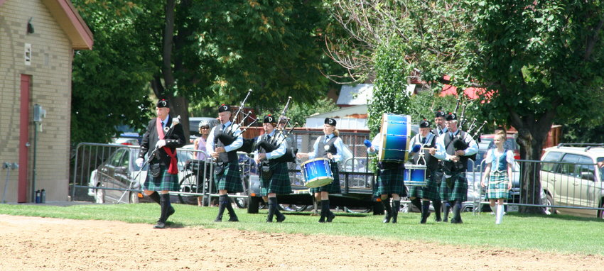 The Denver & District Pipe Band, accompanied by Highland dancers, make their way onto the field to perform during the Cody's Wild West during this year's Buffalo Bill Days.
