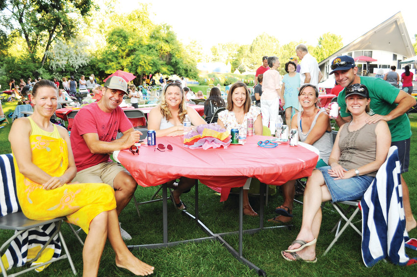 A group sits around a table at a customer appreciation night put on by a local business in late July at the Cherry Knolls pool. The Steller Group Real Estate, a business started by a man who grew up in the Cherry Hills neighborhood of Centennial, held this pool party with entertainment and food.