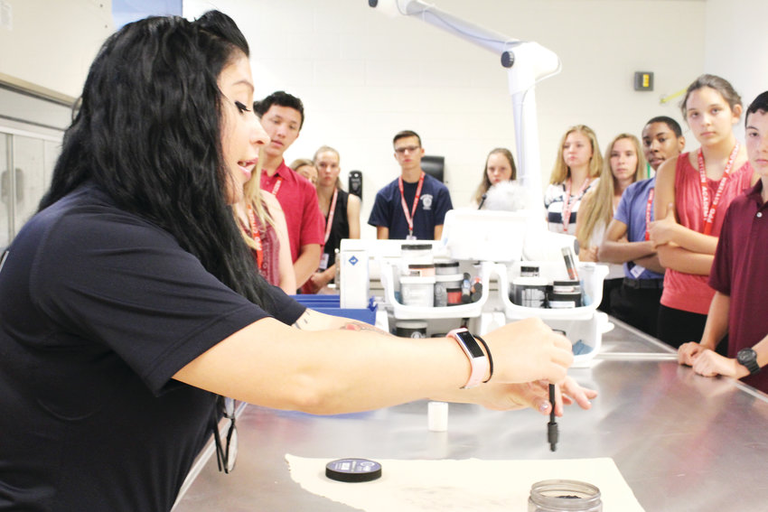 Evidence technician Reanna Sanchez shows students at the Youth Academy the tools the department uses to dust for fingerprints and other tactics for gathering evidence. Sanchez said the department has been able to trace a single fiber of fabric from a bag to identify its owner, who was a possible suspect in a case.