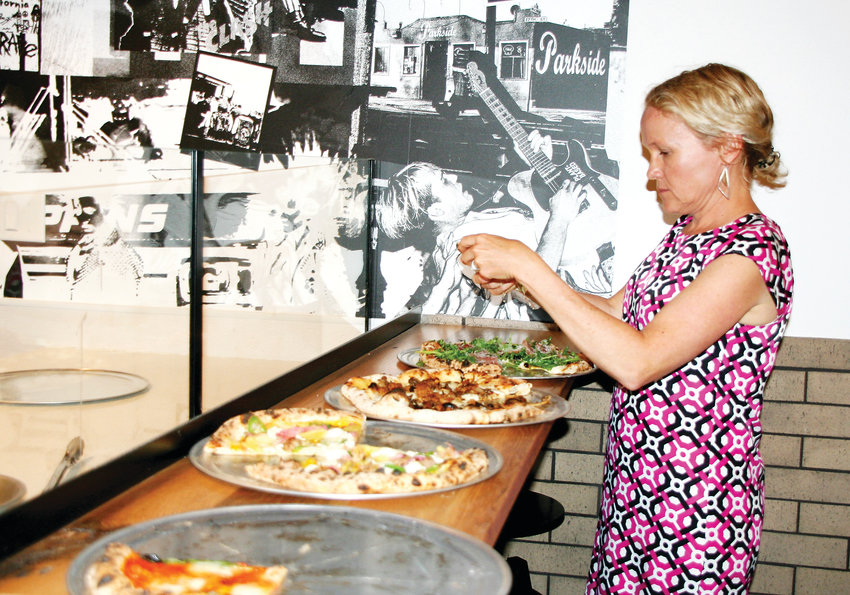 Audrey Waugh selects a piece of pizza from Fringe Pizza's selection during Tributary Food Hall & Drinkery's preview night on July 30. Tributary, 701 12th St., became Golden's first food hall when it opened on Aug. 2.