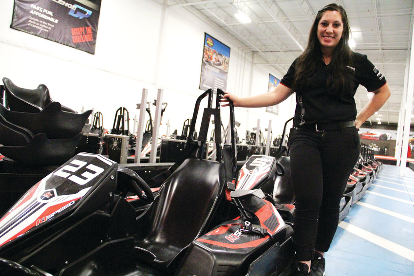 Nichole Sarno, assistant manager, stands next to karts at K1 Speed. Staff members race the karts, too, she said.