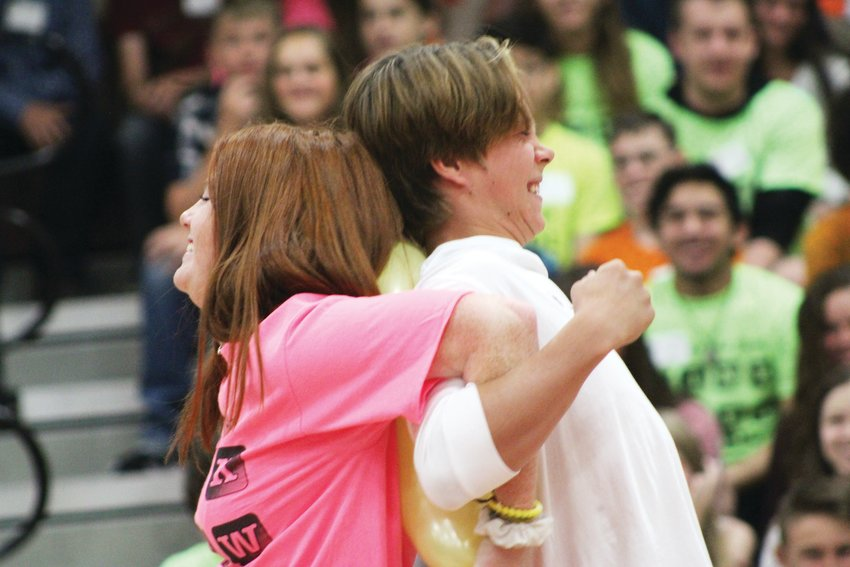 Senior Jenna Wallace and freshman Dawson Hadwiger team up to pop a balloon during an orientation assembly for new freshmen at Ponderosa High School Aug. 7.