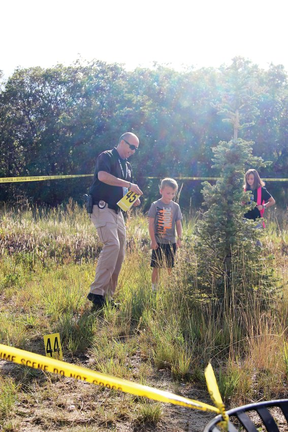 "Ryker Moorman, 8, and his 10-year-old sister Cambria, hunt for evidence in a ""crime scene"" set up by the Castle Rock Police Department at National Night Out."