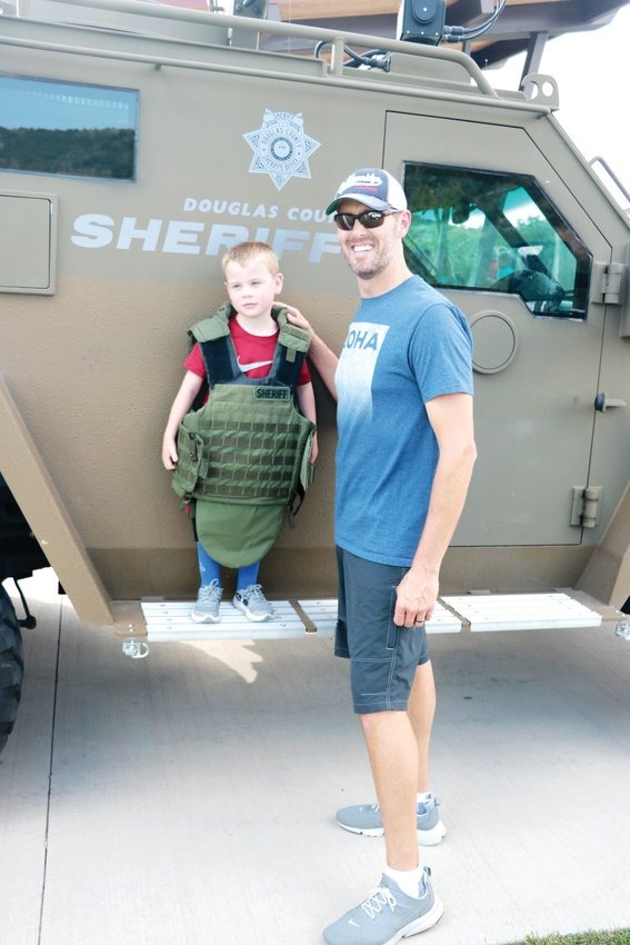 Costner Copeland stands with his father, Shawn, near a SWAT vehicle at National Night Out in Castle Rock on Aug. 6.