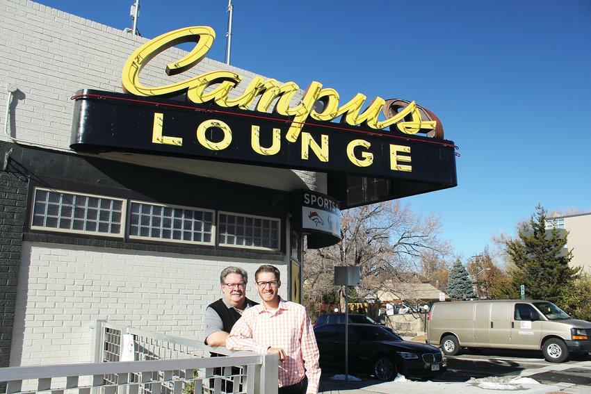 Dan and Jeff Nickless stand below the famous Campus Lounge neon sign in this file photo. The father and son reopened the neighborhood bar in October.