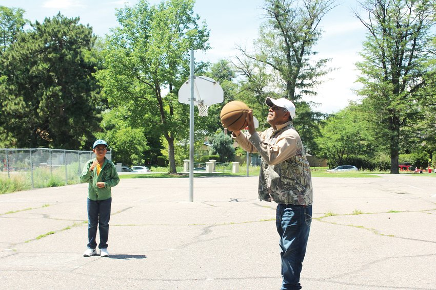 Efrain Camas, right, plays basketball at Washington Park with his two sons, Fabian, pictured, and Efrain. Experts say that one aspect of a healthy community is access to open spaces for exercise.