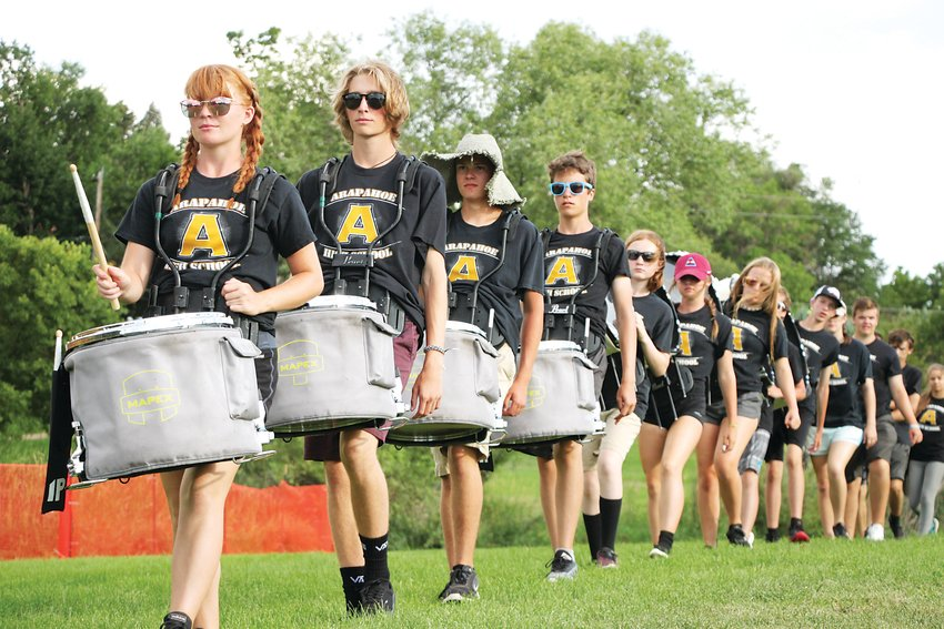 The Arapahoe High School Warrior Band drum line marches toward the stage.