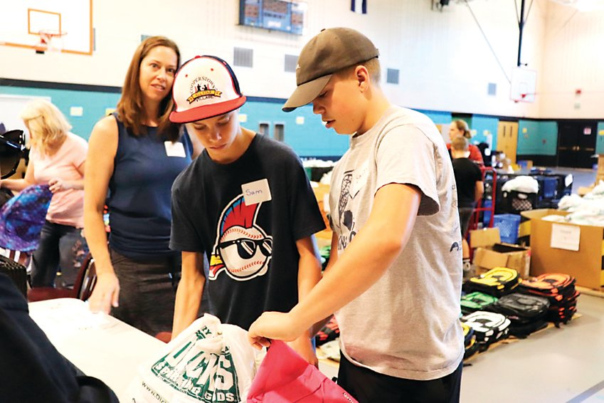 "13-year-old volunteers Sam Allin, left, and Sam Lyall pass out school supplies at the Action Center event. Both said they have also volunteered in previous years. ""It was a great experience and I'm excited to do it again,"" Allin said."
