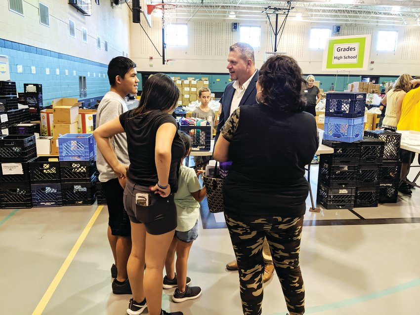 Superintendent Jason Glass talks with Loretta Ornelas and her grandchildren about the upcoming school year. Glass and the superintendents before him have attended the event for years, he said.