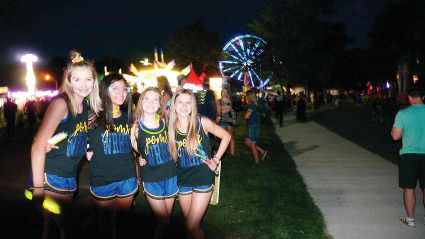 The Carnation Festival is one of Wheat Ridge High School Pom Squad's biggest fundraising events of the year. Some of the members were out enjoying the night and slinging glow sticks for a buck to the sea of people passing by.