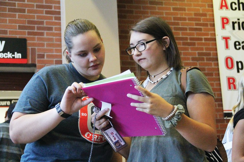 Alexis Conaway, left, helps freshman Mimi O'Brien find her way on Aug. 12, the first day of the year at Eaglecrest High School. Conaway, a senior, is a member of Link Crew, a group of students at high schools who help welcome freshmen.