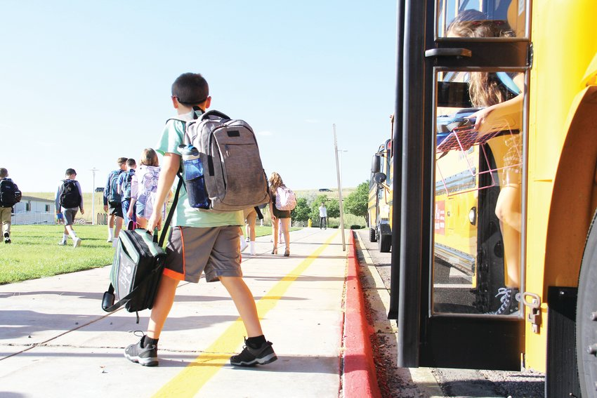 Kids walk off the school bus at Liberty Middle just outside east Centennial on the first day Aug. 12.