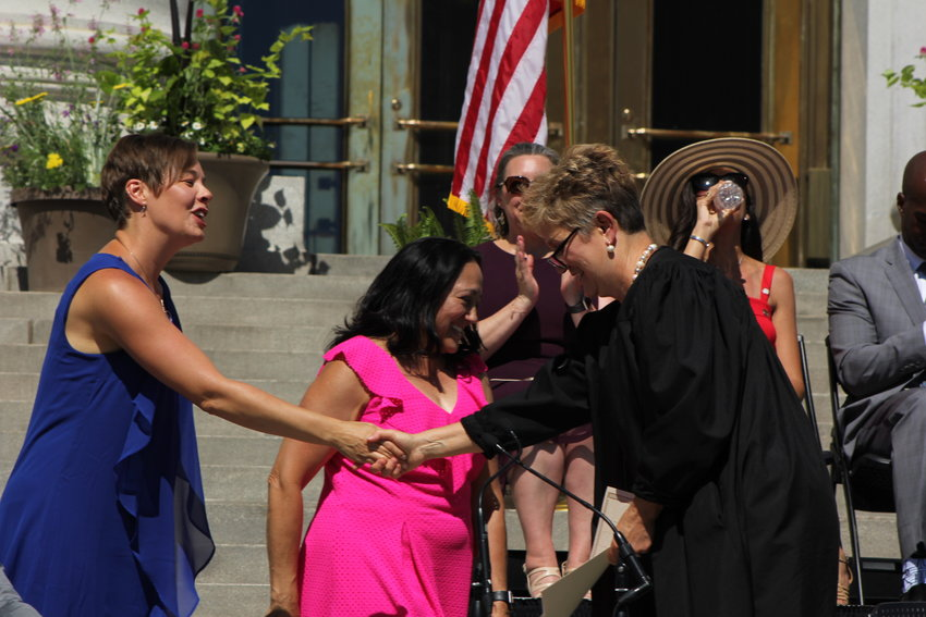 Robin Kniech, left, shakes Judge Theresa Spahn's hand. Spahn swore in new council members on July 15. She was appointed as the presiding judge of Denver County Court in 2016 by Mayor Michael B. Hancock.