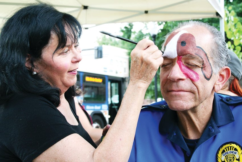 Sue Buckner of Suz-Q-Z face painting paints a dog on Golden Police Chief Bill Kilpatrick's face on Aug. 6 at the Golden Police's National Night Out event, which takes place annually in Parfet Park. Bucker has been painting the chief's face at the event for years, and each year, does a new and unique painting.