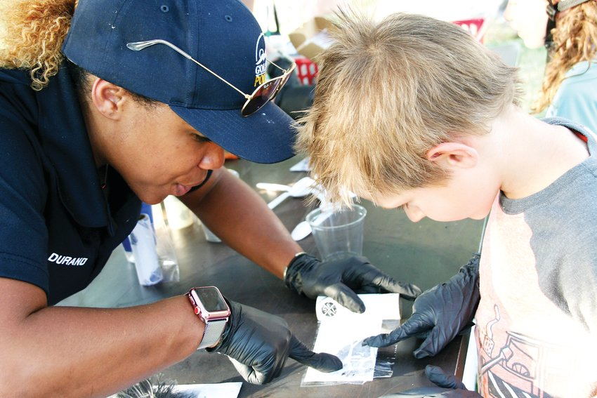 Tanner Kiedrowski, 6, of Golden works with Latara Durand, who works in the Golden Police Department's crime scene investigation, on fingerprinting at the Golden Police Department's National Night Out on Aug. 6 in Parfet Park.