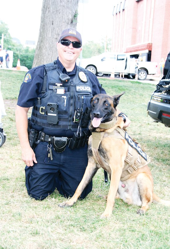 Golden Police Officer Shawn Henslee gets his picture taken with Mao on Aug. 6 at the Golden Police's National Night Out event. Mao is a 3-year-old Belgian Malinois that joined the department in January and is Golden's only police dog.